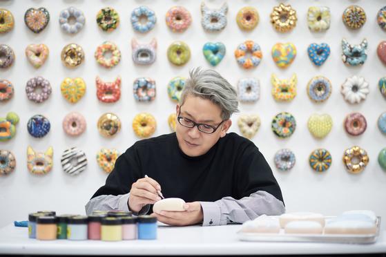 작은 도넛에 그림을 그려넣고 있는 김재용 작가. 그는 도넛으로 '희망'을 빚는다. [사진 학고재갤러리]