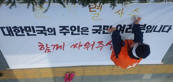 이은재 한국경제당 대표가 전날인 12일 '혈서'를 쓰고 있다. 연합뉴스