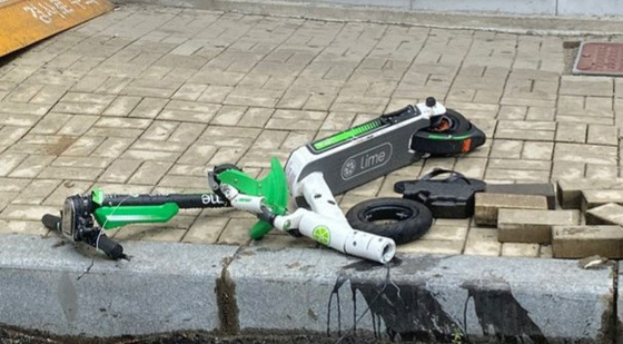 지난 12일 오전 부산 해운대구 한 도로에서 차량과 충돌해 박살난 '라임' 공유 전동 킥보드. 이 사고로 킥보드 운전자가 숨졌다. [연합뉴스]