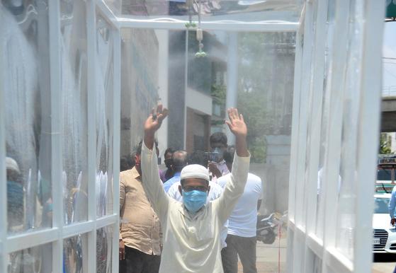 인도 방갈로르에서 한 남성이 시장 입구로 들어가기 위해 비닐로 가려진 터널을 지나고 있다. [신화=연합뉴스]