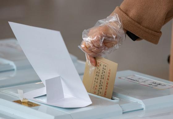 제21대 국회의원선거 사전투표 마지막 날인 11일 오후 서울 용산구 서울역 대합실에 마련된 남영동 사전투표소에서 시민들이 투표함에 용지를 넣고 있다. [뉴스1]