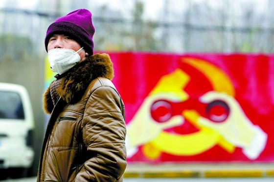 코로나바이러스가 발생한 직후인 지난 1월 중국 상하이. 한 남성이 변형된 중국 공산당의 상징 그림이 그려진 벽화 앞을 마스크를 쓴 채 지나가고 있다. [로이터=연합뉴스]