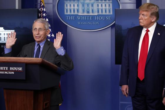 """앤서니 파우치 알레르기전염병 연구소장이 14일 백악관 브리핑에서 전날 CNN 방송에서 """"2월 조기 폐쇄조치를 했더라면 많은 사람을 구했을 것""""이라고 한 것과 관련해 """"가정적 질문에 대한 답변""""이며 """"반발이 컸다는 것은 단어 선택을 잘못했다""""고 인정했다. 도널드 트럼프 대통령은 이후 """"그를 해고하지 않을 것""""이라며 """"훌륭한 사람""""이라고 물러섰다.[AP=연합뉴스]"""