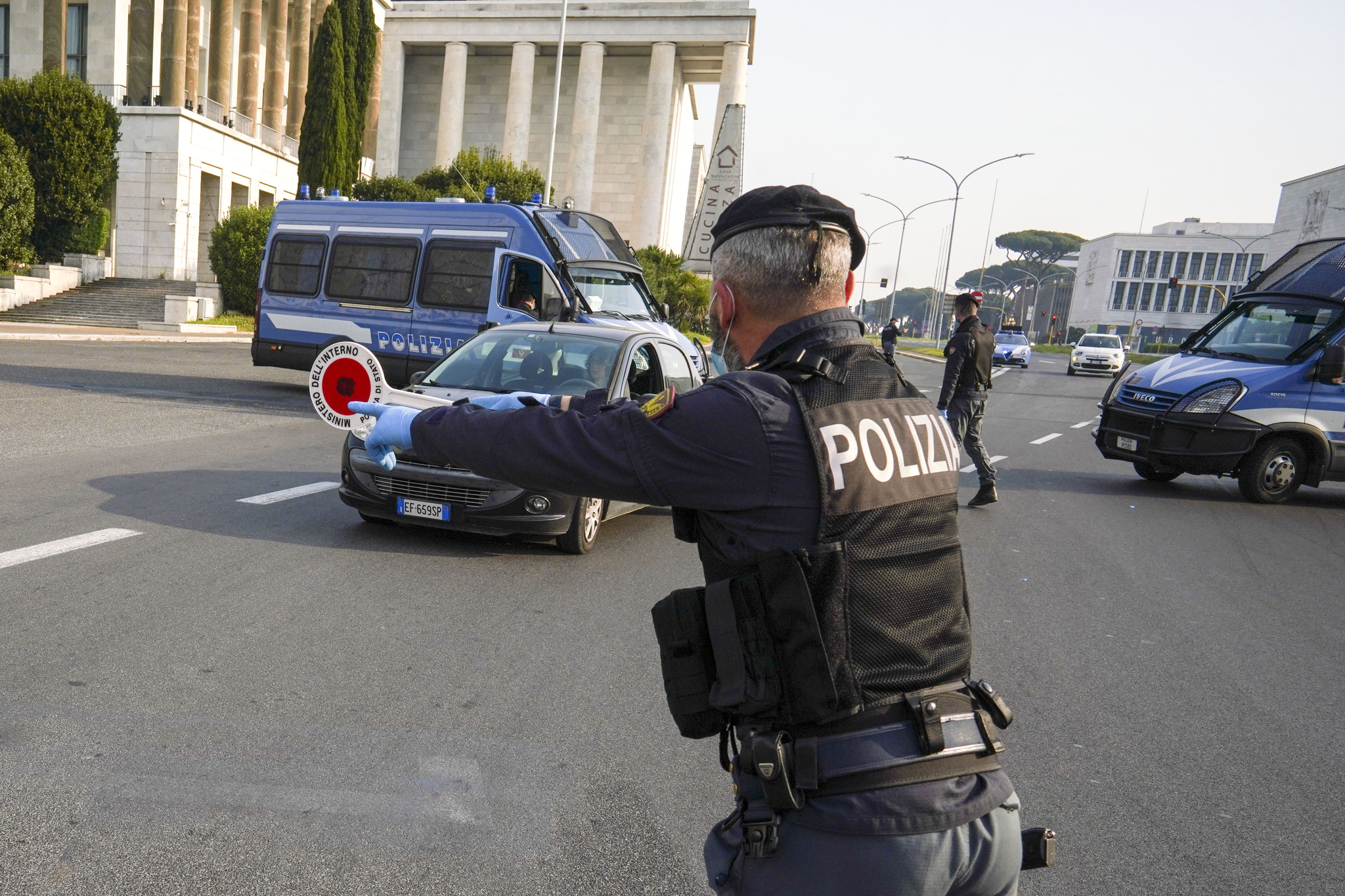 신종 코로나바이러스 감염증(코로나19) 확산 차단을 위해 이동제한령이 발동 중인 이탈리아 로마에서 13일(현지시간) 경찰이 도로를 운행하는 차량을 향해 정지 신호를 보내고 있다. AP=연합뉴스