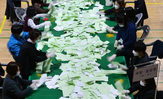 제21대 국회의원선거가 끝난 15일 오후 대전 한밭체육관에 마련된 개표소에서 개표사무원들이 총선 후보들의 투표용지를 분류작업 하고 있다. 김성태 기자