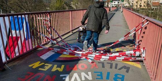 쇼핑백을 든 한 남성이 독일과 프랑스 국경지역에 놓여진 '우정의 다리'를 건너고 있다. [AP=연합뉴스]