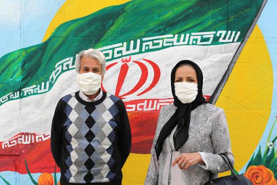 마스크를 쓴 이란인들이 이란 국기가 그려진 테헤란의 벽화 앞에서 포즈를 취하고 있다.[AFP=연합뉴스]