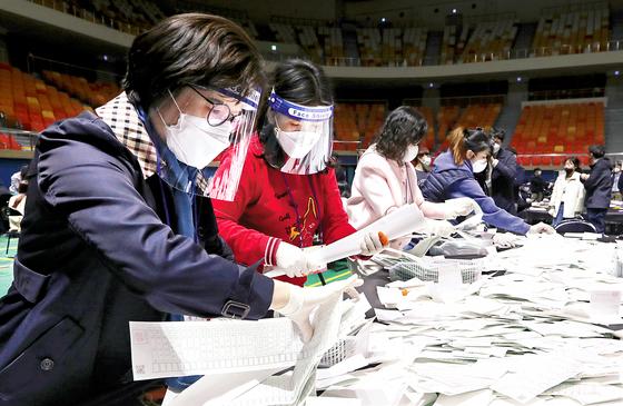 15일 광주광역시 서구 염주체육관에서 안전 마스크를 쓰고 투표용지를 분류하고 있다. [연합뉴스]