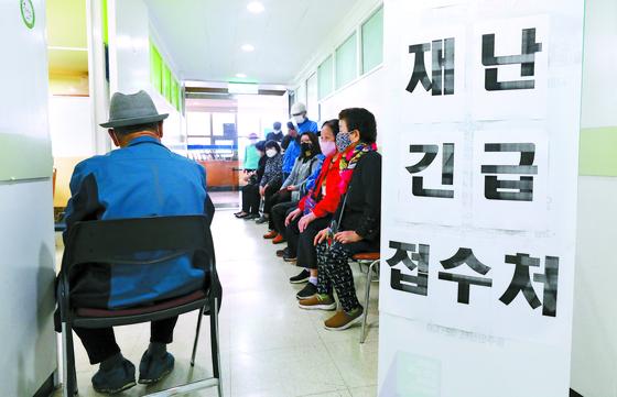 서울시 재난긴급생활비 현장접수가 시작된 16일 서울시내 한 동주민센터를 찾은 주민들이 접수를 위해 줄지어 기다리고 있다. 뉴스1