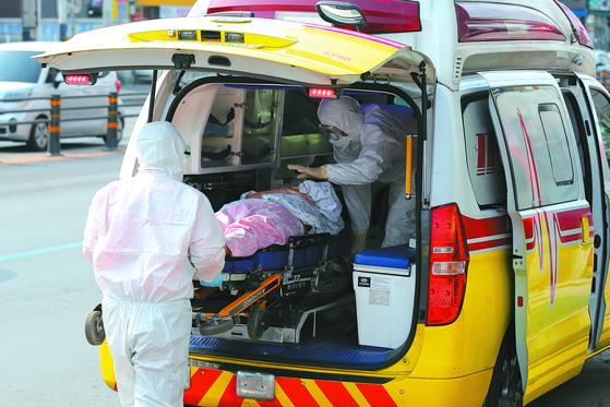 119구급대원이 코로나19 집단감염이 발생한 대구의 한 요양병원 환자를 격리병동으로 후송하기 위해 구급차에 태우고 있다. 뉴스1