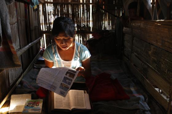 13세 소녀, 완. 바나나 줄기를 얼기설기 엮어 만든 집 안 유일하게 책상과 책이 보였다. 완은 가진 것 중 가장 소중한 것이라며 후원자의 편지를 꺼내 보여주었다. [사진 허호]