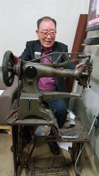 전남대학교에 12억원을 기부한 김병양 어르신이 자신의 손때가 묻은 공업용 재봉틀을 어루만지고 있다. 사진 전남대학교