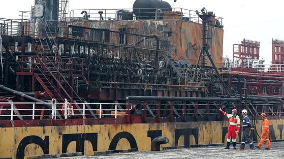 지난해 9월 30일 오후 울산시 동구 염포부두에서 폭발 화재가 발생한 석유제품운반선 '스톨트 그로이란드'호 관계자들이 화재 선박을 살펴보고 있다. 뉴스1
