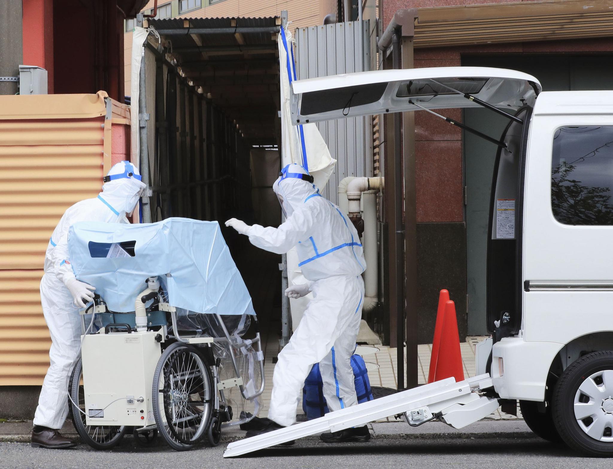 지난 21일 일본 기후현 하시마시에서 보건 당국자들이 신종 코로나바이러스 감염증(코로나19) 환자를 호텔로 이송하고 있다.   일본은 병상 부족 문제를 해소하기 위해 경증 환자는 호텔 등에, 중증 환자는 의료기관에 수용하는 방안을 추진하고 있다. 연합뉴스