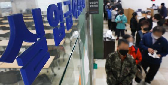 지난 21일 서울 중구 서울지방고용노동청에서 구직자들이 실업급여설명회를 듣기 위해 줄지어 서 있다. [뉴스1]
