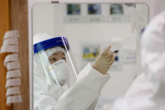 22일 신종 코로나바이러스 감염증(코로나19) 대응 지역거점병원인 대구 중구 계명대 대구동산병원에서 근무를 앞둔 의료진이 보호장비를 착용하고 있다. [뉴스1]