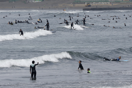지난 21일 가나가와현 후지사와시 쇼난 해안에서 서핑객들이 서핑을 즐기고 있다. [AP=연합뉴스]