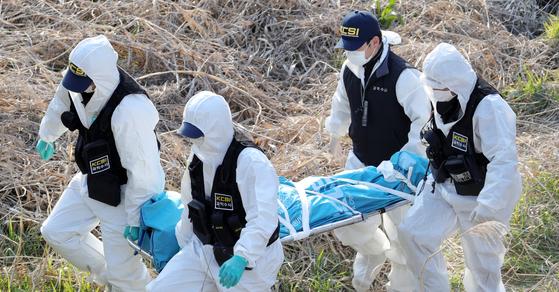23일 전북 진안군 성수면 한 천변에서 지난 14일 실종된 A 씨(34·여) 시신이 발견된 가운데 현장에 나온 전북경찰청 과학수사대 관계자들이 시신을 옮기고 있다. 뉴스1