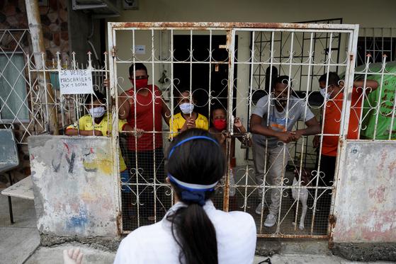 에콰도르 과야킬에서 의료진과 거리를 두고 이야기를 나누고 있는 주민들의 모습. [로이터=연합뉴스]