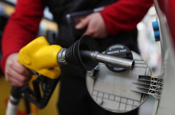 국제유가 급락과 함께 휘발유 가격 하락이 이어지고 있다. 사진은 22일 경남 창원의 한 주유소에서 시민이 주유하는 모습. 연합뉴스