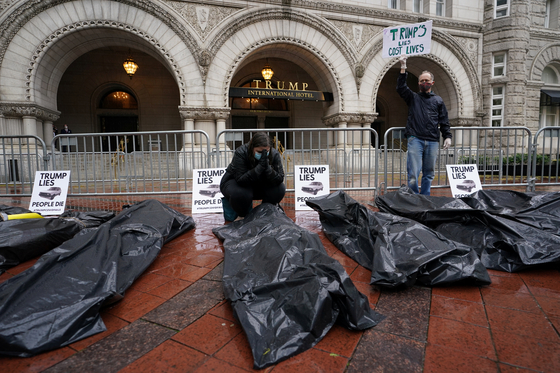 23일 트럼프 행정부의 신종 코로나바이러스 감염증(코로나19) 방역 대책에 비판적인 시위대가 워싱턴 트럼프 인터내셔널 호텔 앞에서 가짜 시체 가방을 두고 시위를 벌이고 있다. REUTERS=연합뉴스