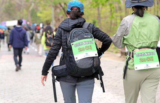 사회적 거리두기 완화 시행 후 첫 주말인 25일 북한산국립공원 입구에서 국립공원공단 관계자들과 아띠산악회 회원들이 코로나19 감염 예방을 위한 안전한 산행 캠페인을 했다. 등산객들이 캠페인 홍보물을 배낭에 부착하고 산행하고 있다. 연합뉴스