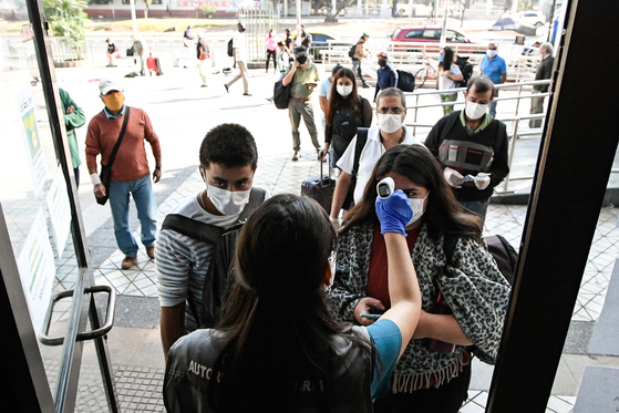 20일 칠레 수도 산티아고에서 버스에 탑승하는 승객을 대상으로 체온을 재고 있다. 신화통신=연합뉴스