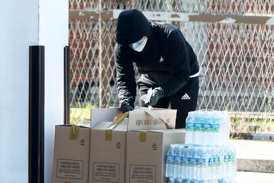 지난 2월 21일 군 내 첫번째 코로나19 확진자가 나온 제주 해군 부대에서 한 군인이 격리 정책에 따라 배달된 도시락 박스를 뜯고 있다. [뉴스1]