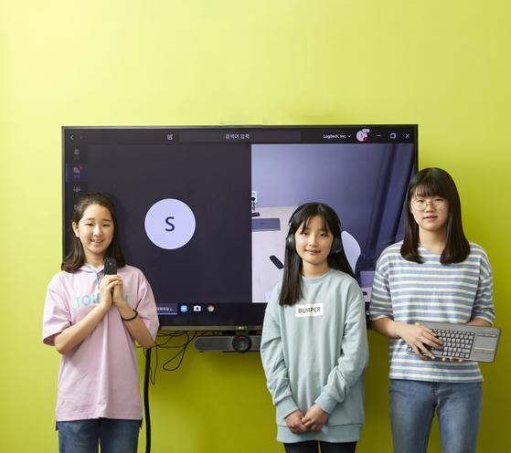 로지텍 화상회의 솔루션 체험관을 찾은 한채연·임서하·박한나(왼쪽부터) 학생기자가 화상회의 기기인 리모컨·무선 헤드셋·무선 키보드를 들고 포즈를 취했다.