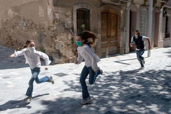 코로나19 차단을 위해 강력한 봉쇄령을 시행해 온 스페인에서 26일(현지시간) 6주 만에 어린이 외출이 허용됐다. 이날 바르셀로나 거리에서 마스크를 쓴 어린이들이 아빠와 함께 뛰어놀고 있다. AFP=연합뉴스