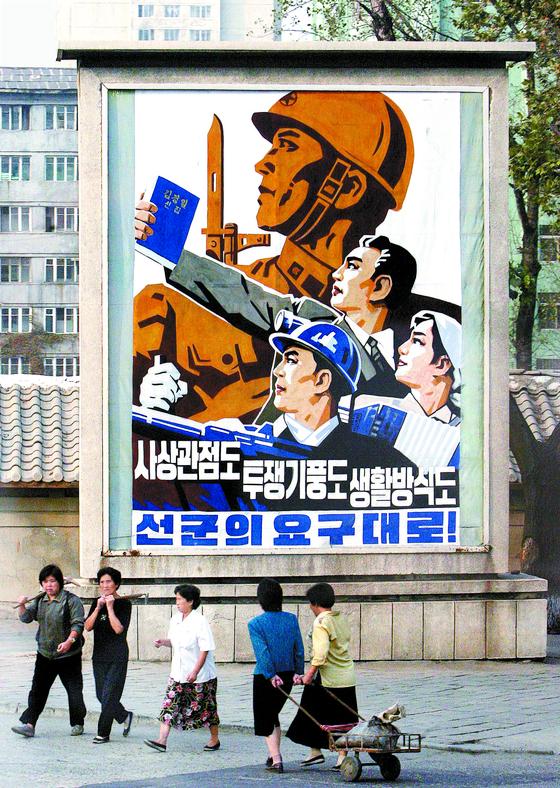 북한 주민의 인권을 외면한 한국 정부의 대북 정책은 장기적으로 한반도 평화에 도움이 안 된다는 지적이 나온다. 사진은 선군 노선을 찬양하는 선전 포스터를 지나치는 평양 시민들. [중앙포토]
