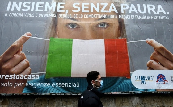이탈리아 나폴리 거리에서 이탈리아 국기를 신종 코로나바이러스 감염증(코로나19) 예방 마스크로 표현한 대형 포스터 앞으로 한 남성이 지나고 있다. [AFP=연합뉴스]