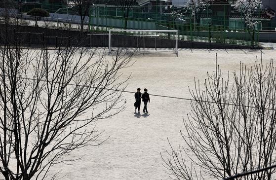 신종 코로나바이러스 감염증(코로나19) 확산 우려로 초·중·고 개학이 미뤄지는 1일 오후 서울 시내의 한 초등학교 운동장을 학생들이 걷고 있다. 뉴스1