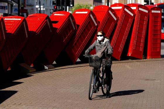 코로나19 시대에 접촉을 피하기 위한 이동수단으로 자전거가 각광받고 있다. 영국 런던에서 마스크를 한 여성이 자전거를 타고 이동하고 있다. [로이터=연합뉴스]