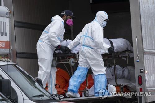 미국 뉴욕 브루클린의 한 장례식장에서 29일(현지시간) 직원들이 시신을 냉동 트럭에 옮겨 싣고 있다. AP=연합뉴스