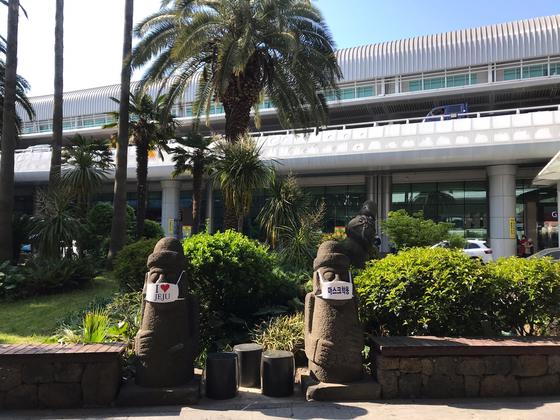 지난 29일 오후 제주국제공항 야외에 설치된 돌하르방에 마스크가 씌워져 있다. 제주를 찾는 관광객 모두가 마스크를 착용하라는 것을 알리기 위해서다. 최충일 기자
