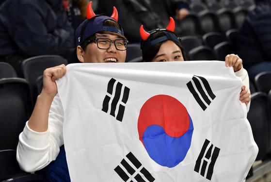 영국 이코노미스트가 OECD 33개국의 코로나 취약도를 분석한 결과, 한국은 14위로 조사됐다. 지난해 영국에서 열린 축구 경기를 보러온 손흥민 선수의 팬들이 태극기를 들어 응원하고 있다. [EPA=연합뉴스]