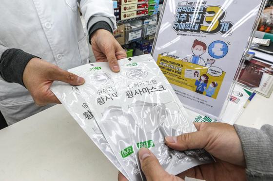 27일 서울 시내의 한 약국에서 시민들이 공적마스크를 구매하고 있다. 정부는 이날부터 공적 마스크 구매 수량을 주간 1인당 2매에서 1인당 3매로 확대한다. 5월3일까지 일주일간 시범 운영하고, 수급에 문제가 없다고 판단되면 '1인 3매' 수량을 유지할 계획이다. 뉴스1