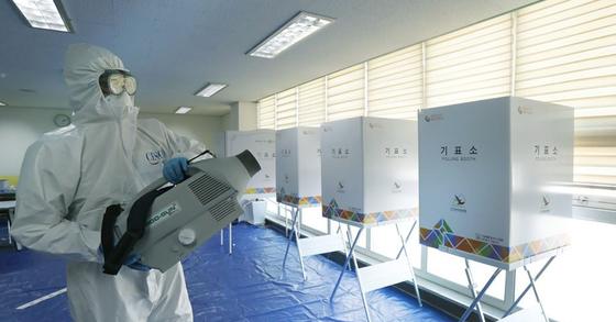 제21대 국회의원 선거를 하루 앞둔 지난달 14일 오후 서울 송파구의 한 투표소에서 방역관계자가 코로나19 확산 방지를 위한 방역을 하고 있다. [연합뉴스]