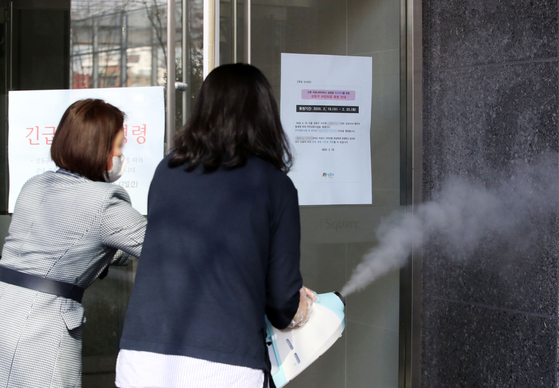 신종 코로나 바이러스 감염증(코로나19) 32번째 확진자가 발생한 19일 오전 서울 성동구 한 어린이집에서 관계자들이 출입문 손잡이를 방역하고 있다. [뉴시스]