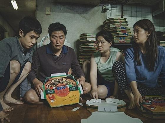 영화 '기생충'의 한 장면. 기택(송강호)의 가족들이 반지하 집에 모여앉아 피자박스를 접고 있다. [사진 CJ엔터테인먼트]