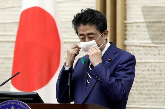 지난달 17일 총리관저에서 열린 기자회견을 시작하기 직전 아베 신조 일본 총리가 마스크를 벗고 있다. 로이터=연합뉴스