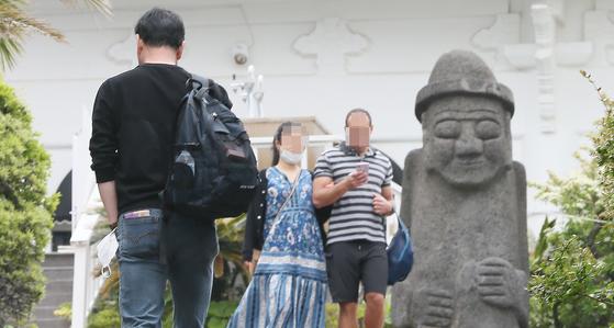 황금연휴 나흘째인 3일 제주도 중문해수욕장에서 마스크를 벗은 관광객들이 길을 걷고 있다. [연합뉴스]