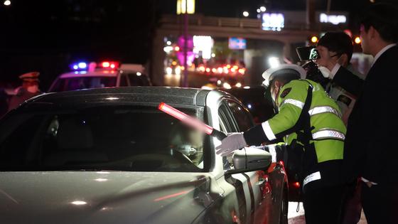 지난달 20일 저녁 경기도 광주시 역동삼거리에서 경찰이 일회용 덮개를 씌운 비접촉식 음주감지기를 활용해 음주단속 시범운영을 하고 있다. [뉴스1]