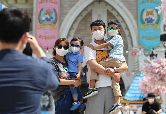 어린이날을 하루 앞둔 4일 오후 서울 송파구 롯데월드에서 한 가족이 마스크를 쓴 채 기념사진을 찍고 있다. 뉴스1