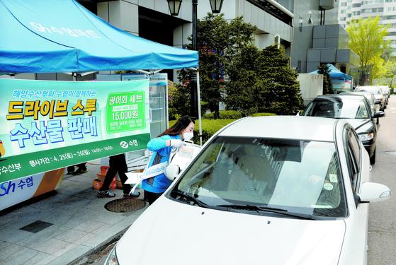 코로나19로 수산물 소비 행태가 달라지고 있다. 지난달 26일 서울 송파구 수협중앙회 본사의 '드라이브 스루 수산물 판매' 행사에서 시민들이 차량 등을 이용해 광어회 세트를 사고 있다. [뉴스1]