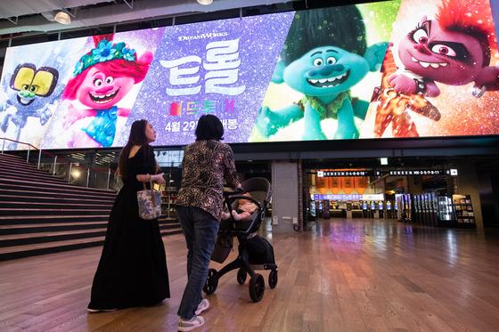 어린이날 서울 코엑스 메가박스 극장에서 애니메이션 '트롤: 월드 투어' 광고 아래로 관람객이 유모차를 밀고 지나가고 있다. 이 작품은 가족 관객의 호응으로 황금연휴 흥행 1위에 올랐다. [뉴스1]