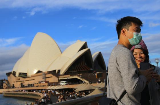 지난 3월 호주 시드니 오페라하우스에서 관광객이 마스크를 쓴 채 관광을 하고 있다.[EPA=연합뉴스]