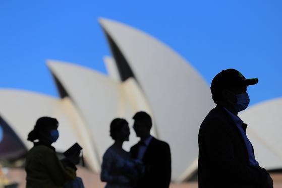 지난 3월 호주 시드니 오페라 하우스 앞에서 관광객들이 마스크를 쓴 채 관광을 하고 있다.[EPA=연합뉴스]