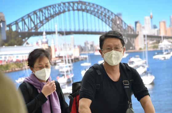 지난 1월 호주 시드니 하버 브리지 앞에서 중국인 관광객이 마스크를 쓴 채 관광을 하고 있다.[AFP=연합뉴스]